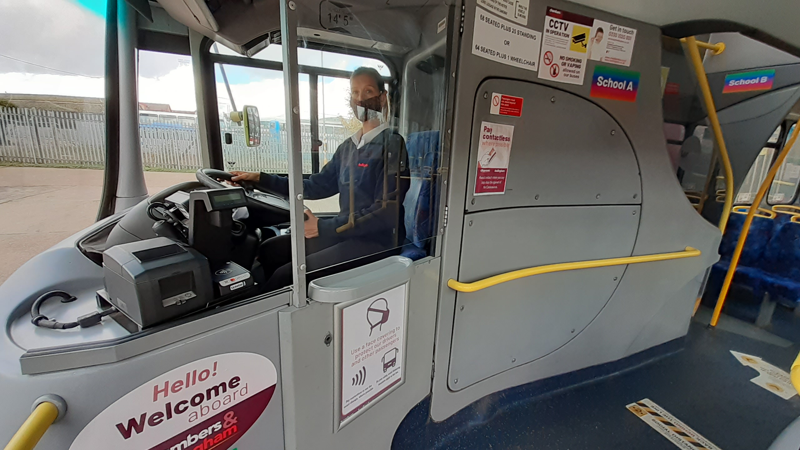 Photo of a bus driver wearing a mask behind a protected cab screen