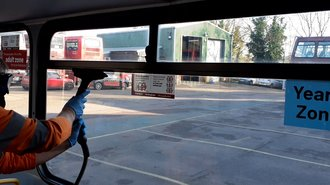 Photo of bus windows being steam cleaned