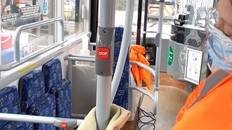 Photo of a bus pole being sanitised